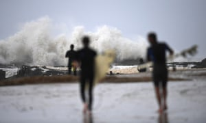 Surfers prepare to take advantage of wild surf conditions at Snapper Rocks on the Gold Coast on Sunday.