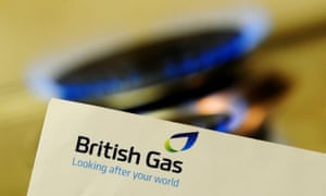 A British Gas bill held in front of a lit gas hob.