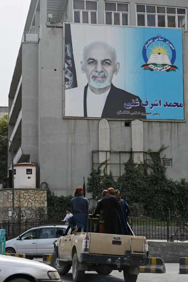 Taliban fighters patrol the streets of Kabul, overlooked by a poster of former Afghanistan president Ashraf Ghani.