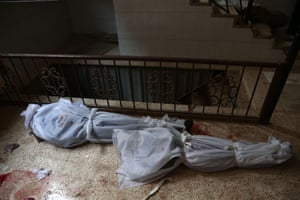 The bodies of civilians who were killed are seen lying on the ground at a makeshift morgue