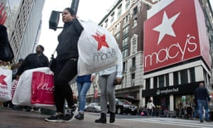 Shoppers carry bags as they cross a pedestrian walkway near Macy's in Herald Square in New York.