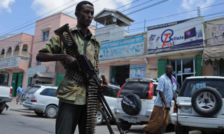 Man with machine gun as part of government security patrol on streets of Mogadishu