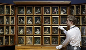 London, England A Christie's employee looks at 48 wax reliefs in a German brass-mounted and satine-crossbanded cherrywood cabinet estimated at between £40,000-£60,000