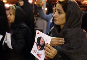 Women hold up photographs in memory of Qasem Souleimani during a night time vigil in Tehran.