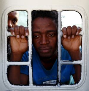 Migrants look out of a window on the Medecins Sans Frontier rescue ship Bourbon Argos.