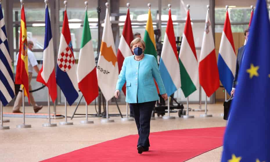 A masked Angela Merkel arrives walks along a red carpet in front of flags of European nations and the European Union at an EU summit in Brussels.