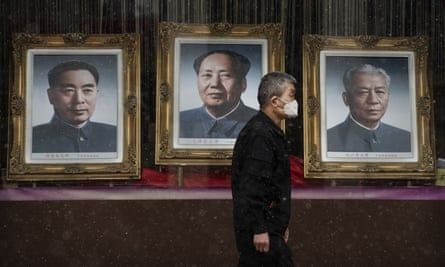 A man passes a picture of Mao Zedong in a nearly empty shopping area in Beijing. The death toll from the coronavirus outbreak has risen to 1,523.