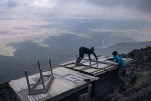 Volcanologists clean the solar panels of their monitoring facilities