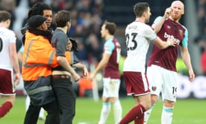James Collins argues with a pitch invader during the match between West Ham United and Burnley.