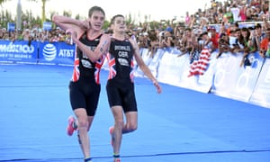 Alistair Brownlee, left, helps his brother Jonny to get to the finish line during the Triathlon World Series event in Cozumel, Mexico.