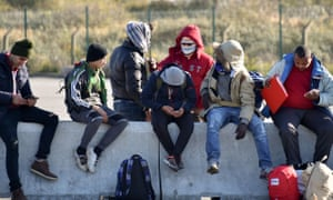 Young migrants wait to board a bus leaving for a reception centre in Calais.