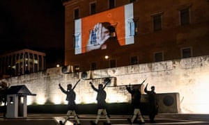 """Presidential guards walk past a projection on the Greek parliament building in Athens reading """"No to violence"""" for the International Day for the Elimination of Violence Against Women"""