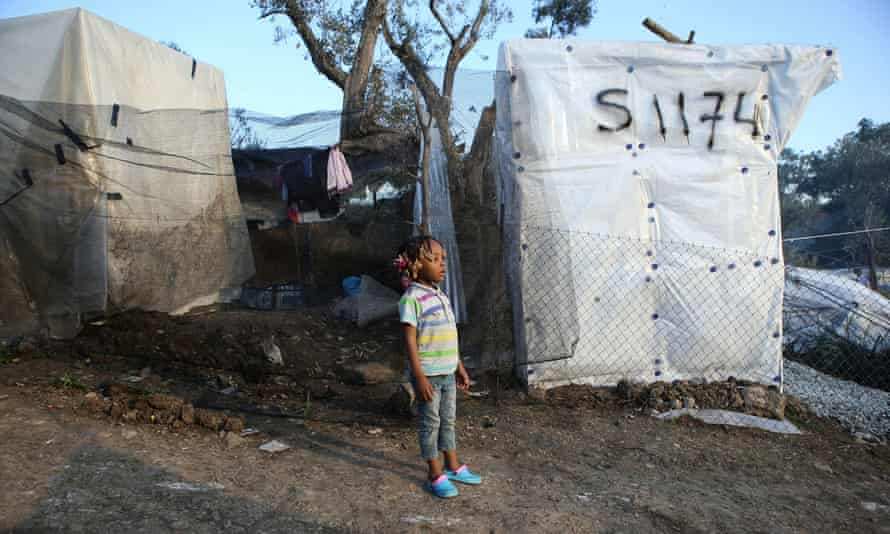A child next to tents on Lesbos, Greece