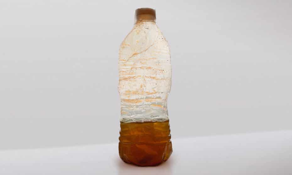 plastic bottle containing discoloured water from a household tap in Flint Michigan