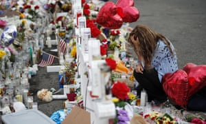 Gloria Garces kneels in front of crosses at a makeshift memorial near the scene of the El Paso shooting, 6 August 2019, in El Paso, Texas.