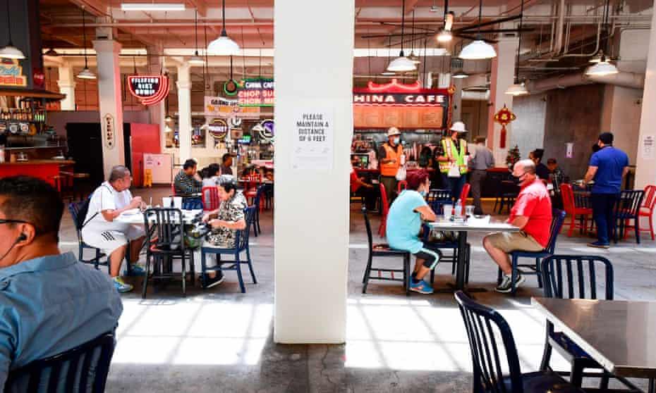 People sit at tables at Grand Central Market in downtown Los Angeles, California, on 24 June amid a record rise in coronavirus cases across the state