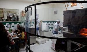 Chefs put pizzas into the over at Naples' L'antica Pizzeria da Michele Forcella. Italy.