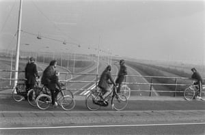 Cyclists on a viaduct overlooking an almost empty motorway