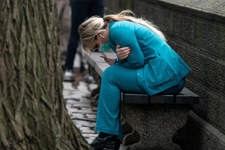 A healthcare worker sits on a bench near Central park in Manhattan.