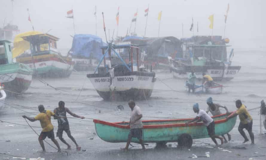 Fishers try to move a boat to safer ground in Mumbai