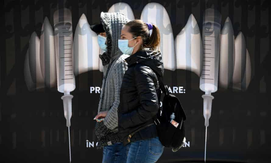 People wearing masks walk by a banner showing syringes as vampire fangs at Bran Castle in Romania