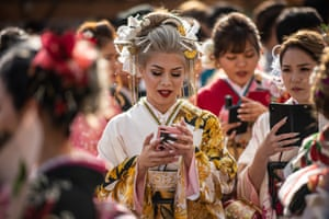 Okinawa, Japan: a woman in a kimono checks her phone before a ceremony on Coming of Age Day