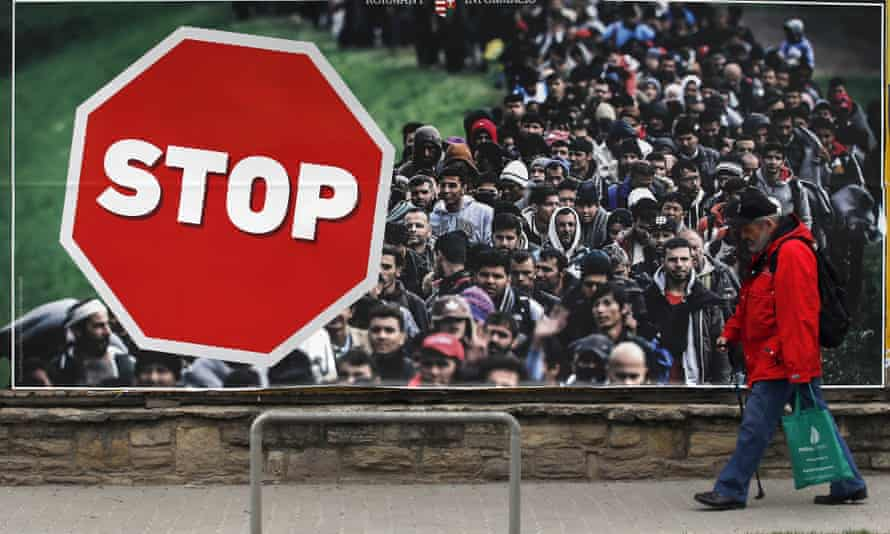 A man walks by an anti-migration billboard from the Hungarian government in Budapest.
