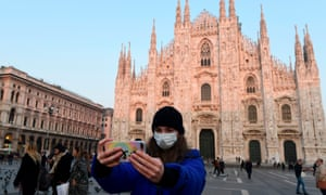 A tourist in a protective face mask takes a selfie outside the Duomo in Milan, as Italy attempts to contain its Covid-19 outbreak.