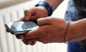 A teenage boy using an iPhone.