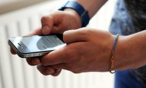 Teenage Boy Using An Apple iPhone 4S