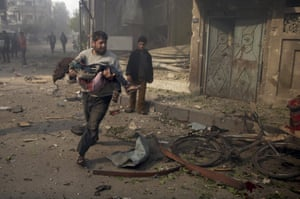 A man carries an injured girl as he rushes away from buildings hit by what activists said were airstrikes by forces loyal to Syria's President Bashar al-Assad, in the Douma neighbourhood of Damascus