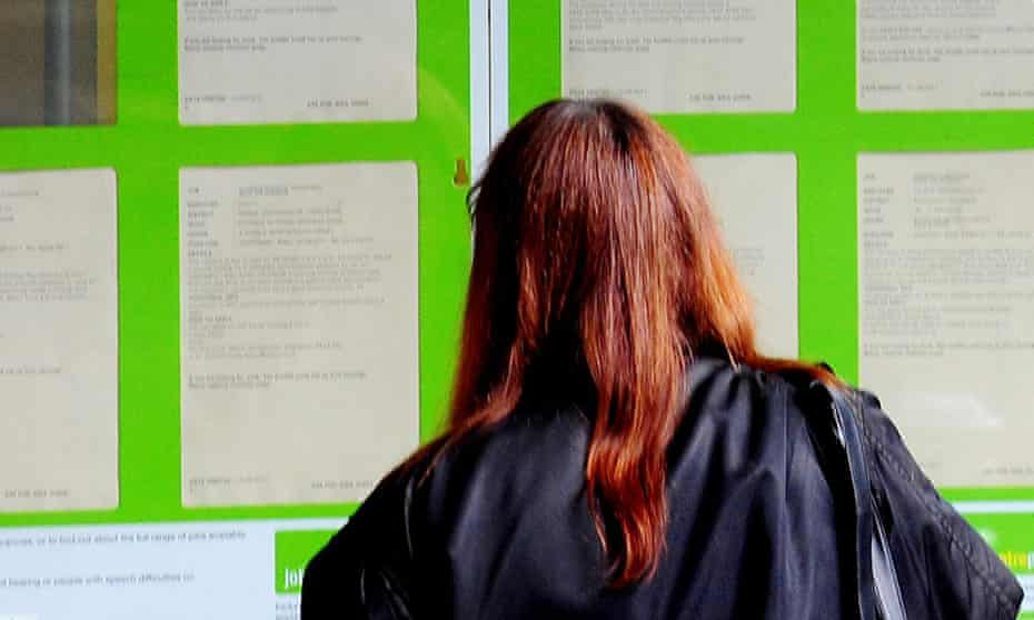 Woman looking into the window of a jobcentre