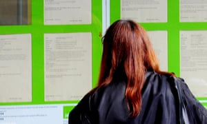 A woman looks into the window of a job centre