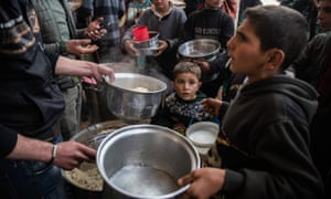 Displaced Syrians wait for hot meal in Idlib, Syria, last month.