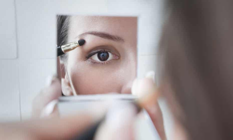 Woman does make-up in a mirror