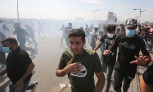 Iraqi protesters run for cover.