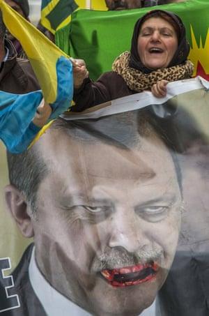 Kurdish protesters hold posters of the Turkish president, Recep Tayyip Erdoğan, outside the EU-Turkey migration summit