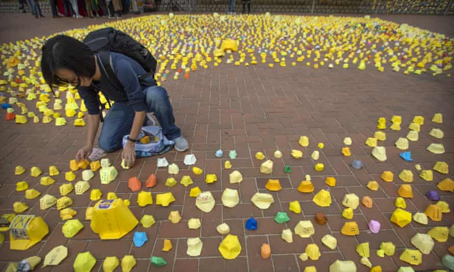 A woman arranges miniature folded paper hard hats during a rally in Hong Kong on Tuesday. Police have frozen funds bound for protesters.