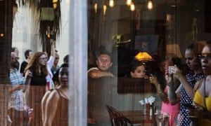 People watch from inside a restaurant as the march passes by