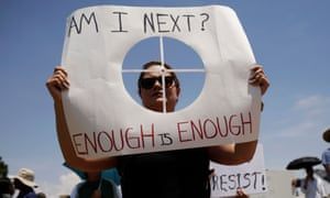 A woman holds a placard bearing the likeness of a shooting target during a rally against the visit of U.S. President Donald Trump after last weekend's shooting at a Walmart store, in El Paso, Texas, U.S., August 7, 2019.