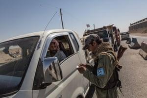 An officer of the Kurdish police checks vehicles
