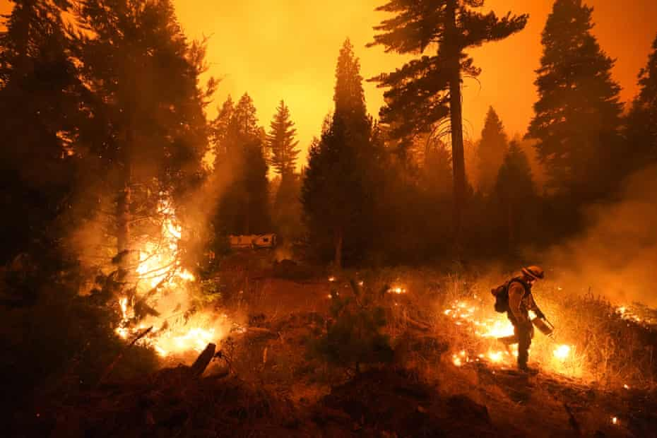 Ricardo Gomez of Cal Fire sets a controlled burn with a drip torch while fighting the Creek fire on 6 September.