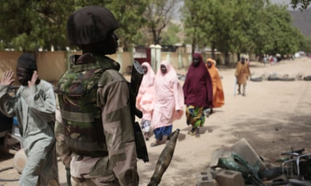In this 2015 photograph civilians walk past a checkpoint manned by Nigerian soldiers in Gwoza, a town newly liberated from Boko Haram.