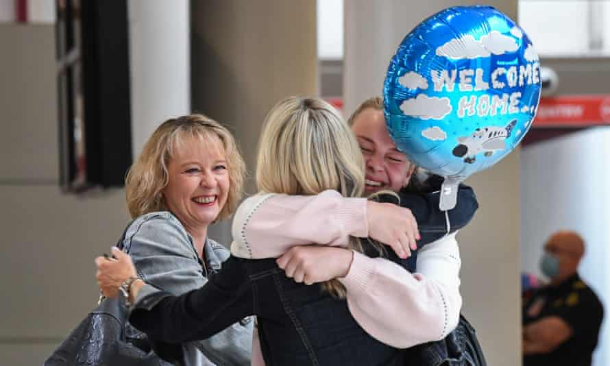 Friends hug one another as they greet each other as they arrive into the international arrivals area at Sydney's Kingsford Smith Airport on October 16, 2020 in Sydney, Australia.