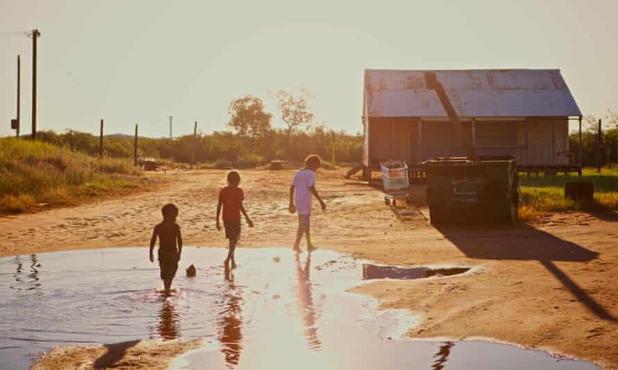 Aboriginal kids walking trough a puddle in Broome, Western Australia.