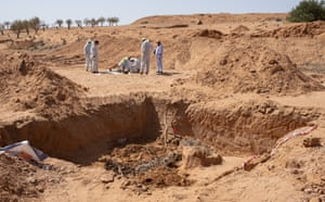 Members of a team who search for and identify missing persons work at the site of a mass grave in Tarhuna, Libya