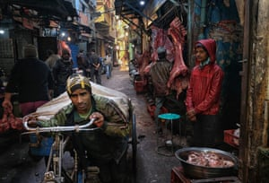 New Delhi, India. A labourer pulls buffalo meat on his bike through a meat market in the old quarters