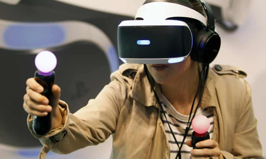 A visitor at the Paris Motorshow tries the PlayStation VR with two Move controllers which act as hands within the virtual environment
