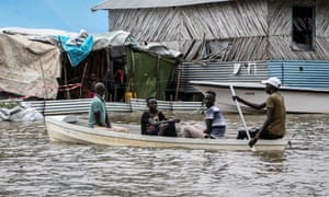 People row through a flooded area in Boma state, South Sudan. At least 76 people have died and over 400,000 people have been displaced since flooding began last month.