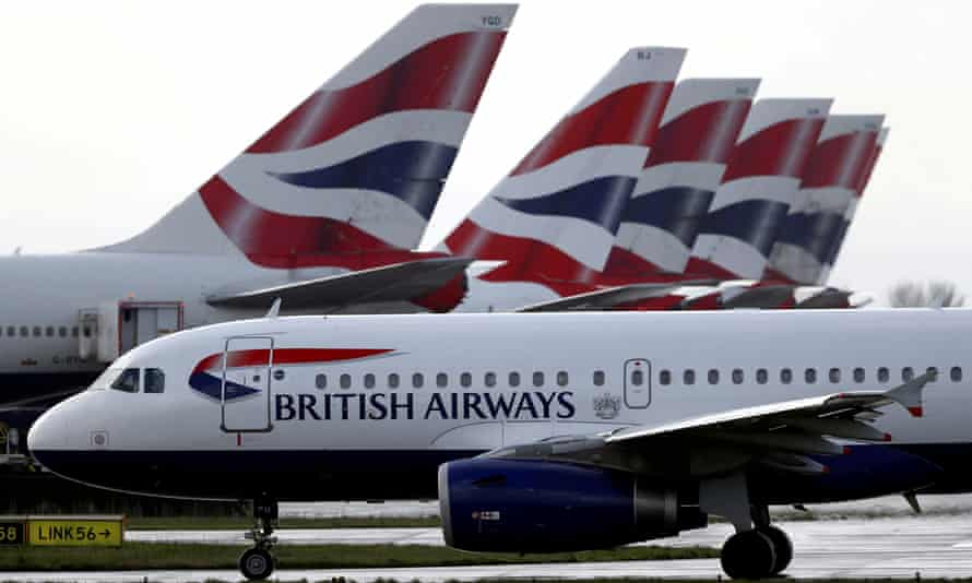 A British Airways plane taxis past tail fins of parked aircraft at Heathrow airport in London